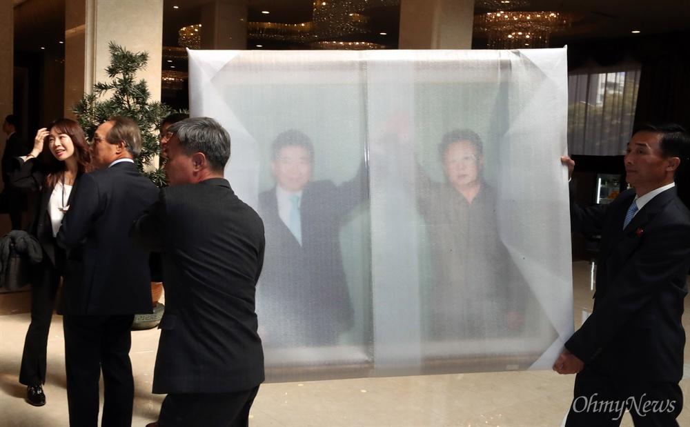 4일 오전 평양 고려호텔에서 관계자들이 '10.4 선언 11주년 기념 민족통일대회'를 위해 남측에서 가져온 2007년 10.4 공동선언 당시 노무현 전 대통령과 김정일 북한 국방위원장의 모습이 담긴 사진을 옮기고 있다.