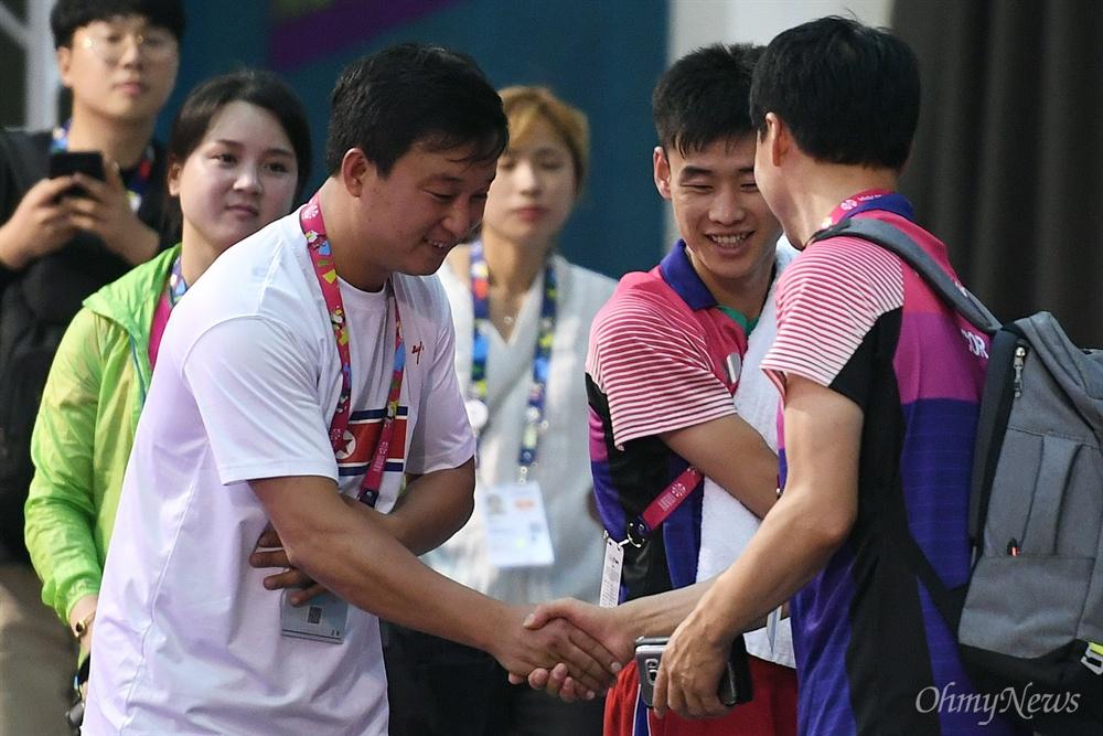 '2018 인도네시아 장애인아시아경기대회' 탁구 남북 단일팀 남측 문창주(오른쪽) 감독과 북측 리철웅(왼쪽) 감독이 5일 오후(현지시간) 인도네시아 자카르타 이컨벤션에서 만나 인사를 나누고 있다. 가운데는 북측 김영록 선수.