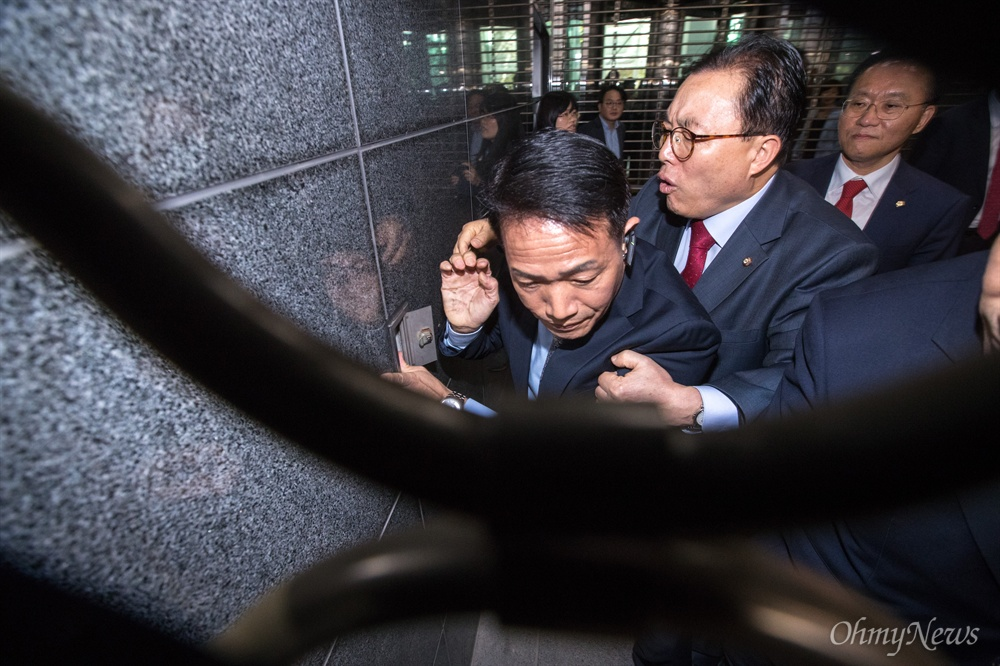 자유한국당 이채익 의원이 18일 오후 서울시청 후문에서 셔터 차단기를 조작하려 던 시 관계자를 저지하고 있다.