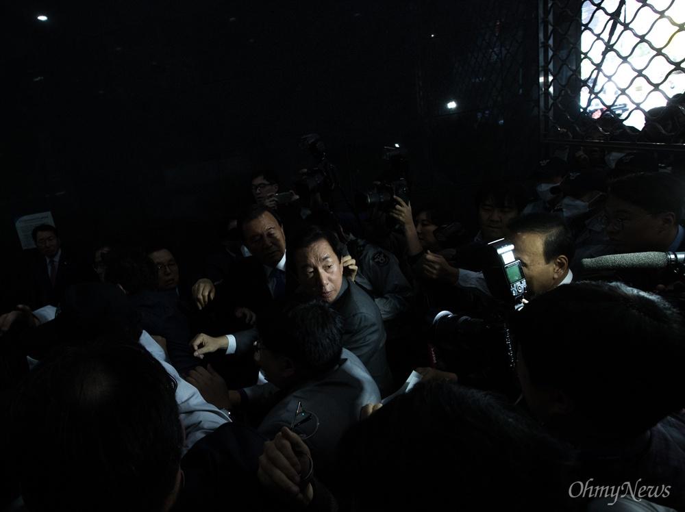 자유한국당 김성태 원내대표가 18일 오후 서울시청 후문에서 막혔던 입구가 임시로 열리자 서울교통공사 '특혜입사' 논란을 규탄하는 기자회견 하기 위해 본청입구 셔터 아래로 들어가고 있다.