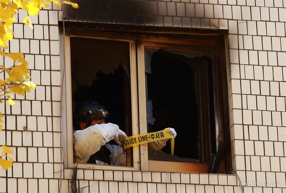 9일 오전 서울 종로구 관수동 한 고시원에서 화재가 발생해 10여명의 사상자가 발생한 가운데, 소방관이 불탄 고시원에서 폴리스라인을 설치하고 있다.