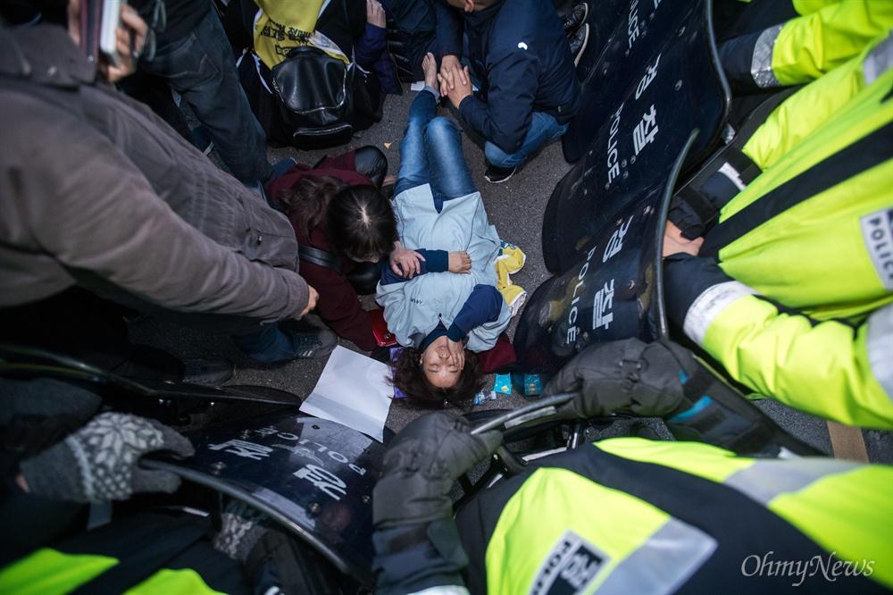 민주노총 비정규직 노동자들이 12일 오후 서울 종로구 정부서울청사 앞에서 청와대로 비정규직 100인 대표단과 문재인 대통령의 직접 면담을 요구 행진을 하던 중 천막농성을 저지한 경찰과 충돌해 부상자가 쓰러져 있다.