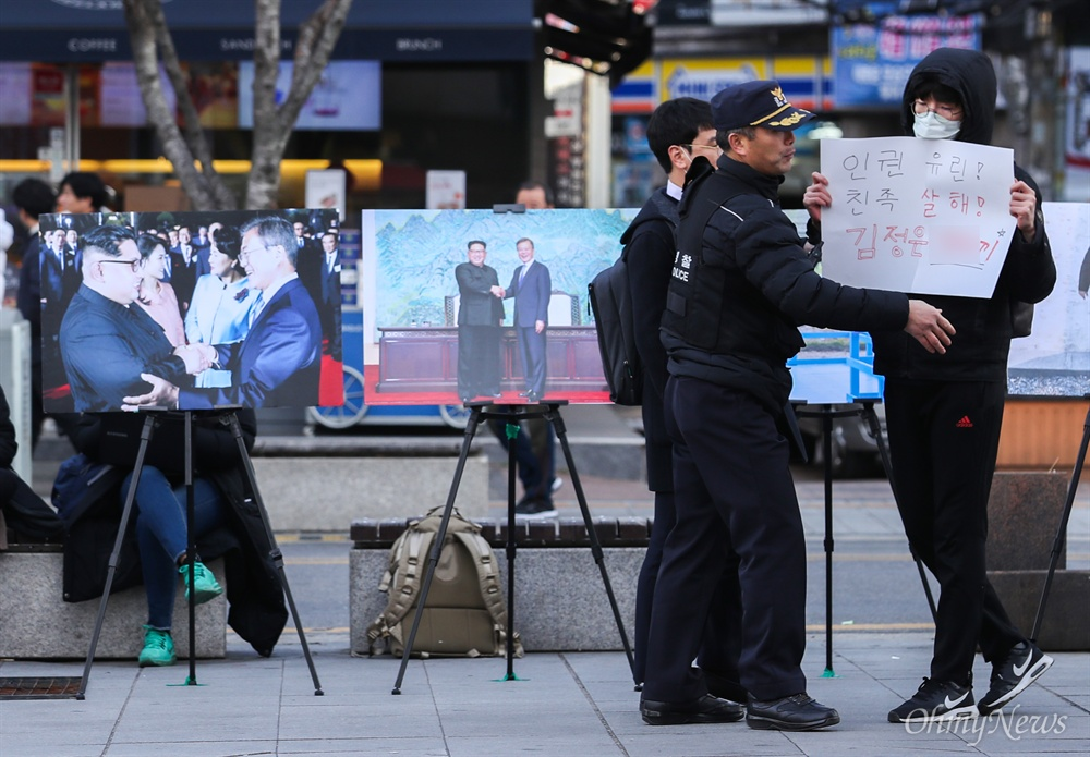 한국대학생진보연합 회원들이 28일 오후 서울 서대문구 신촌 유플렉스 앞에서 김정은 국무위원장의 서울방문 촉구 및 환영 캠페인을 시작하자 김정은 국무위원장 비방 내용이 적힌 피켓을 든 사람이 나타나 경찰이 저지하고 있다.