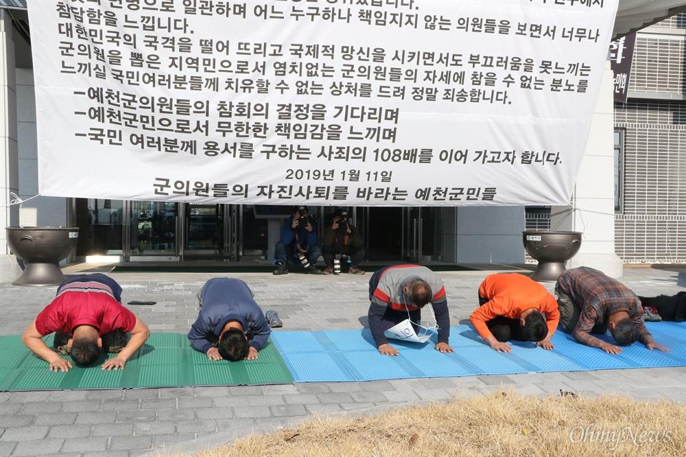 '군의원 잘못 뽑아 죄송합니다' 예천군민들이 11일 낮 예천군의회 앞에서 군의원들의 사퇴를 촉구하는 108배를 올리고 있는 모습.