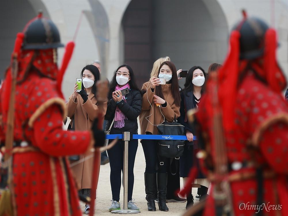 수도권과 전국 곳곳에 미세먼지 비상저감조치가 내려진 14일 오전 서울 경복궁을 찾은 관람객들이 마스크를 착용한 채 수문장 교대식을 지켜보고 있다.