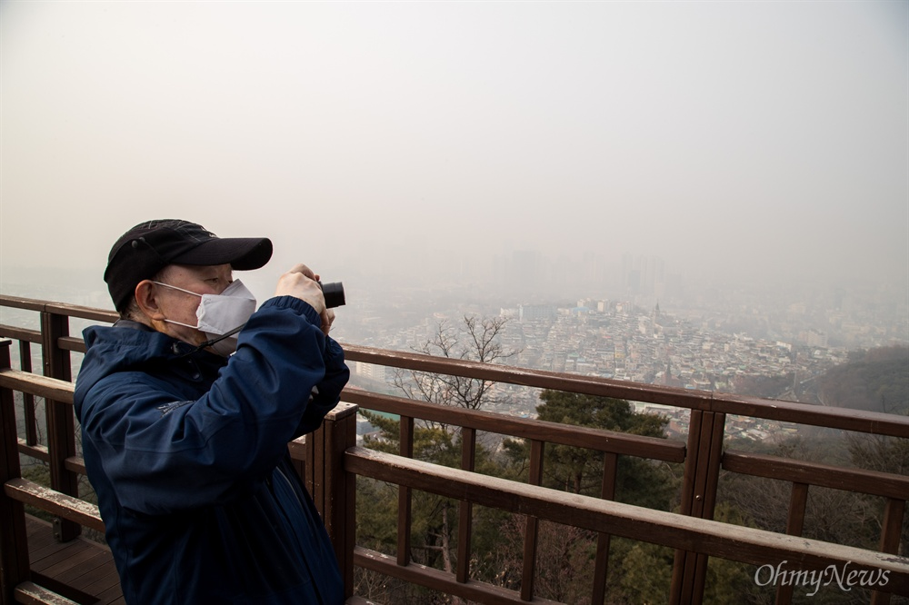 미세먼지가 매우나쁨 수준으로 미세먼지 비상저감조치가 시행 된 14일 오전 서울 남산 일대에서 한 시민이 뿌연 서울 시내 사진을 찍고 있다.