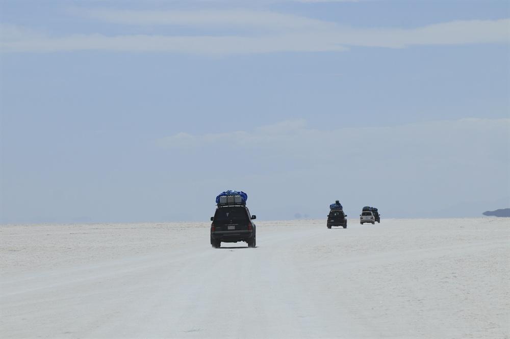 일행을 싣고 우유니 소금사막을 달리는 4륜구동차들 모습