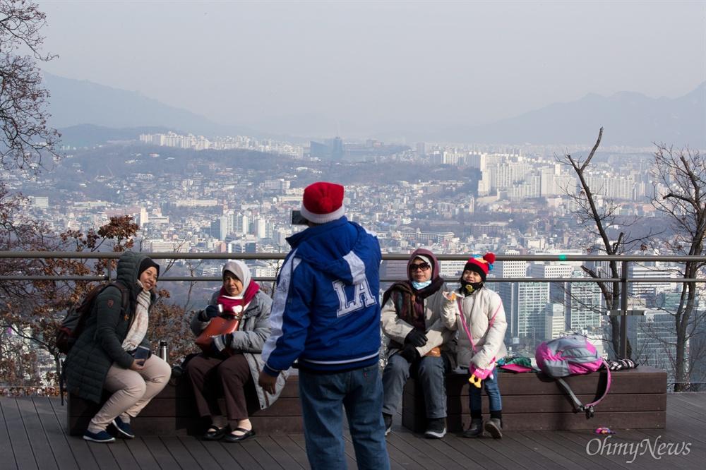 미세먼지가 걷힌 서울 시내를 배경으로 기념사진을 찍는 관광객들.