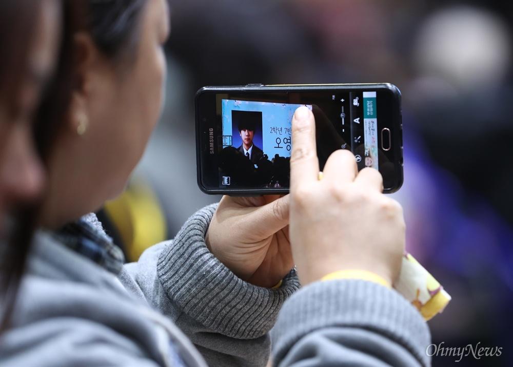 12일 오전 경기도 안산 단원고등학교에서 열린 세월호 참사로 희생된 단원고 학생들의 명예 졸업식에서 영석 엄마 김미화씨가 아들의 사진이 화면에 나오자 사진을 찍고 있다.