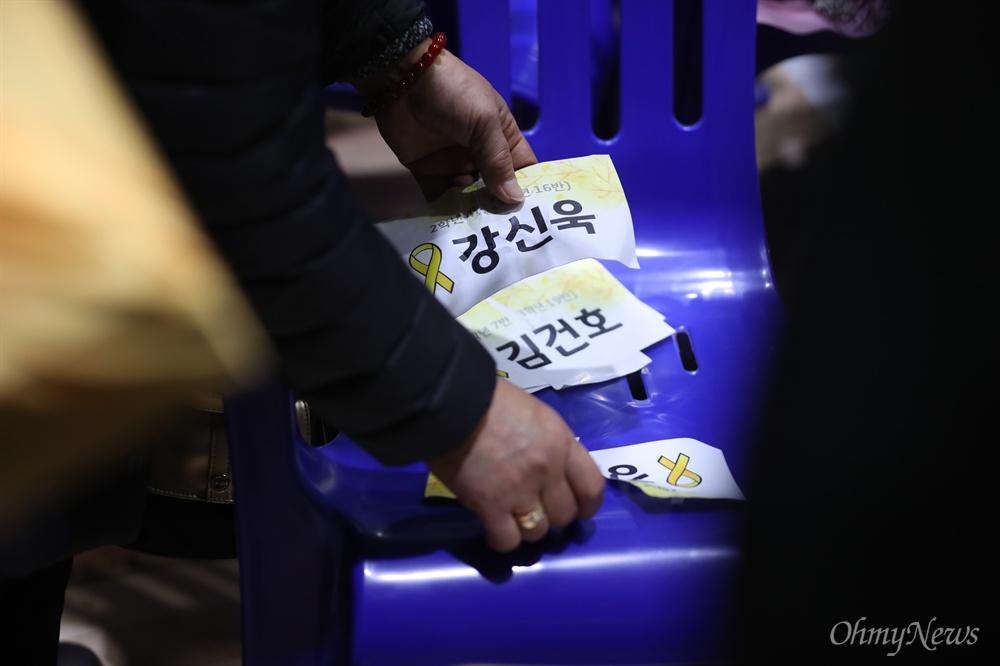 12일 오전 경기도 안산 단원고등학교에서 열린 세월호 참사로 희생된 단원고 학생들의 명예 졸업식에서 한 유가족이 의자에 붙어있던 이름표를 챙기고 있다.
