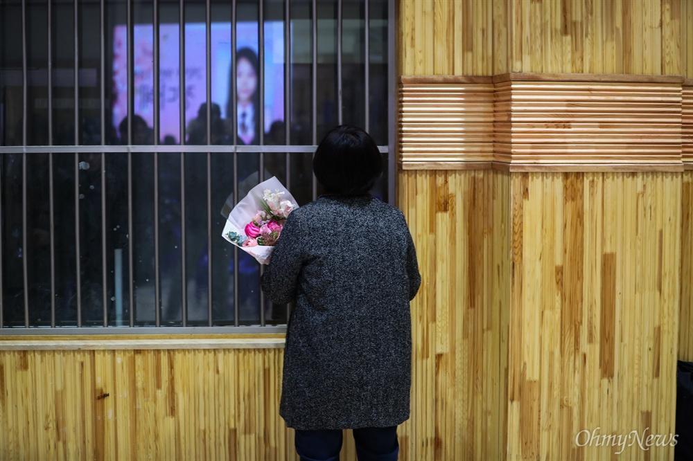 12일 오전 경기도 안산 단원고등학교에서 열린 세월호 참사로 희생된 단원고 학생들의 명예 졸업식에서 한 유가족이 꽃다발을 들고 돌아서 있다.