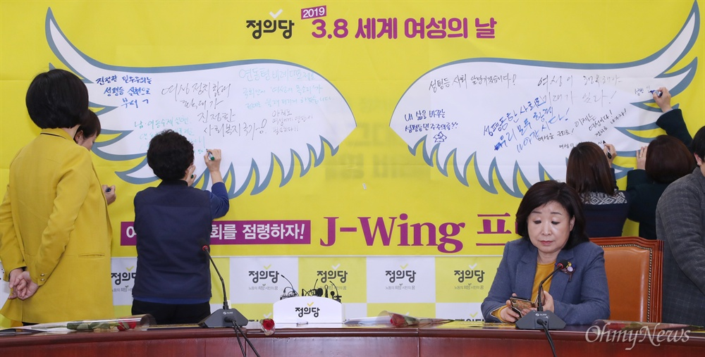정의당 '천사의 날개' 빈칸 메우는 국회 청소노동자 국회 청소노동자 노동조합 김영숙 위원장(왼쪽에서 두 번째)이 6일 오전 정의당 초청을 받아 국회에서 열린 '여성에게 빵과 장미를' 퍼포먼스에 참여했다. 김 위원장도 정의당이 준비한 '천사의 날개' 빈 칸에 세계 여성의 날을 기념하는 메시지를 남겼다. 이날 행사는 3.8 세계 여성의 날을 앞두고 생전 노회찬 의원이 해오던 '여성에게 빵과 장미를' 퍼포먼스를 정의당이 재현하는 취지로 열렸다.