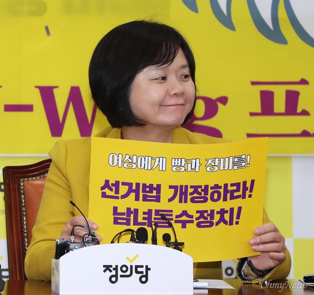 피켓 든 이정미 대표 정의당 이정미 대표가 6일 국회에서 3.8 세계 여성의 날 기념식에 참석해 '여성에게 빵과 장미를! 남녀동수정치! 선거법 개정하라!'라고 적힌 피켓을 들고 있다.