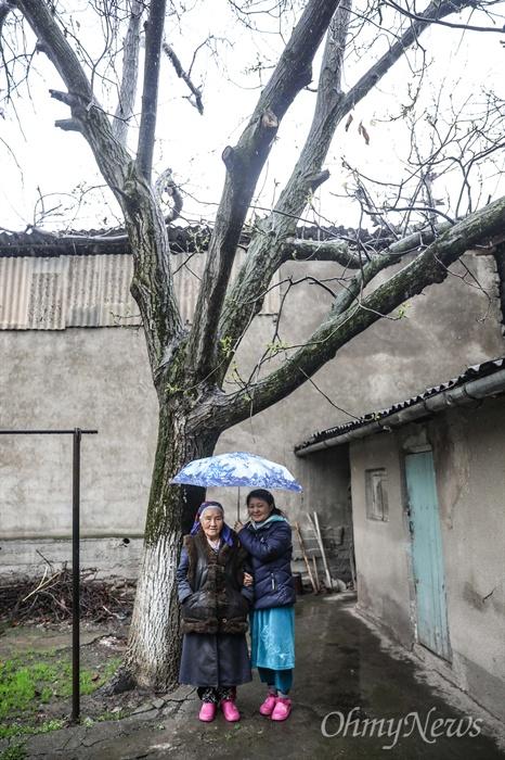 또냐의 아버지가 사랑한 집 앞마당의 나무 앞에서 기념사진을 찍고 있는 최 파밀리아 할머니와 딸 또냐.