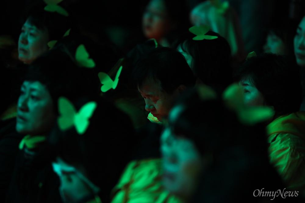 세월호 5주기를 앞둔 13일 오후 서울 광화문 광장에서 열린 세월호참사 5주기 기억문화제에서 공연을 보던 한 유가족이 고개를 떨구고 있다.
