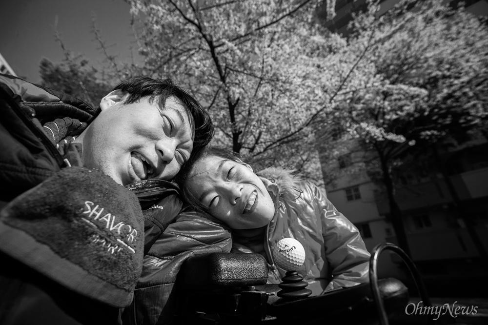 집 앞에 활짝 핀 벚꽃 아래 함께 웃으며 기념사진을 남기는 상우씨와 성은씨.