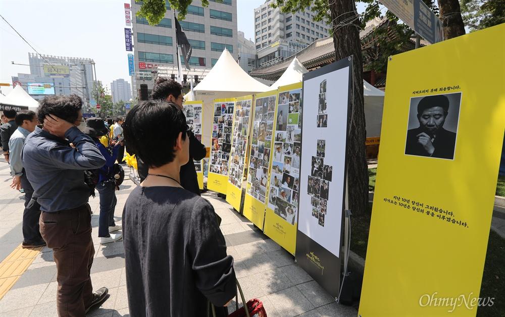 '벌써 10년, 여전히 당신이 그립다' 노무현 대통령 서거 10주기인 23일 오전 서울 덕수궁 대한문앞에 마련된 시민분향소에서 시민들이 고인의 생전 모습이 담긴 사진을 살펴보고 있다.