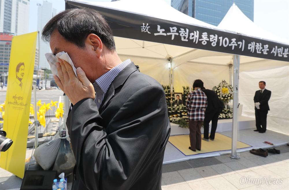 '벌써 10년, 여전히 당신이 그립다' 노무현 대통령 서거 10주기인 23일 오전 서울 덕수궁 대한문앞에 마련된 시민분향소에서 조문을 마치고 나온 한 시민이 눈물을 닦고 있다.