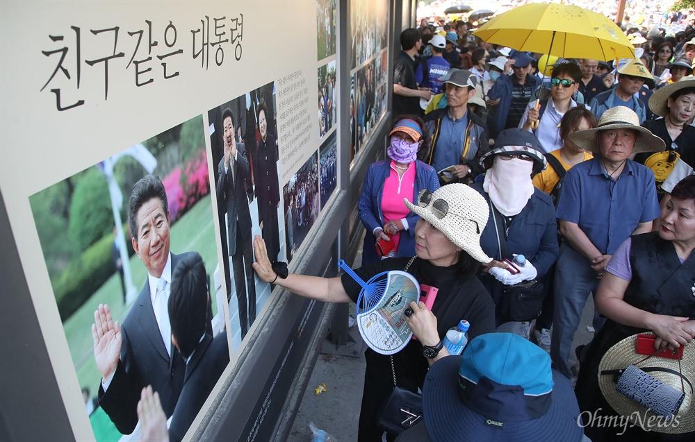 23일 오후 경남 김해 봉하마을에서 열린 '고 노무현 전 대통령 서거 10주기 추도식'에서 추모객들이 노 전 대통령의 생전 모습을 전시한 사진을 둘러보고 있다.