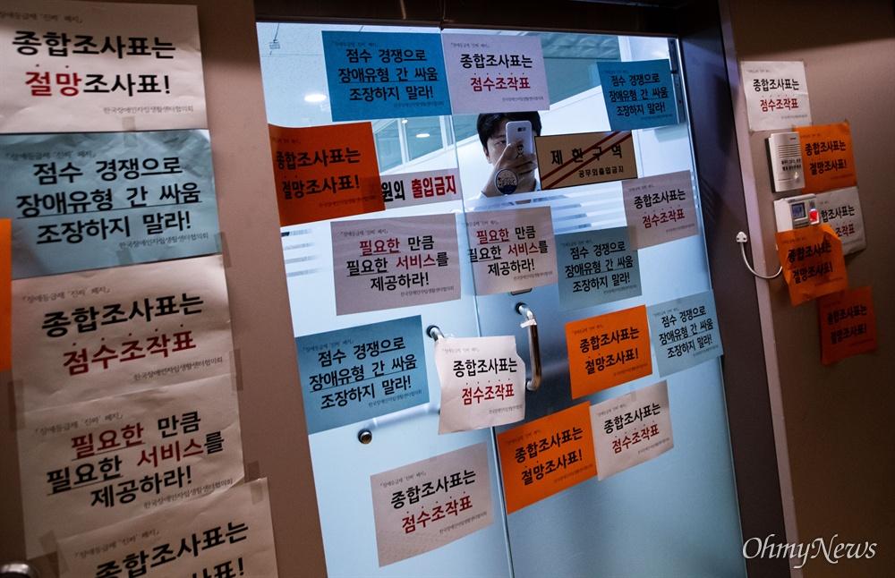 한국장애인자립생활센터협의회 회원들이 14일 오전 서울 종로구 사회보장위원회에서 장애등급제 폐지를 앞두고 종합조사표 전면 수정을 요구하는 농성을 하든 동안 내부에서 직원들이 바깥상황을 살피고 있다.