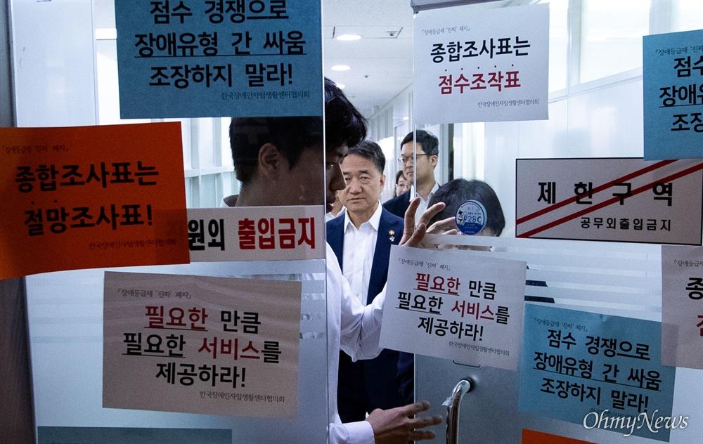 박능후 보건복지부 장관이 14일 오전 서울 종로구 사회보장위원회에서 장애인 종합조사표 전면 수정 요구 피켓이 붙어있는 입구를 빠져 나오고 있다.