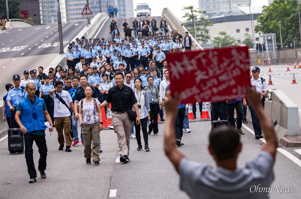 17일 오전 범죄인 인도법(일명 송환법) 폐지를 촉구하는 '검은 행진'에 참가한 홍콩 시민들에게 경찰들이 도로점거 철수를 요구하며 다가오자 한 시민이 손 피켓을 들고 마주하고 있다.