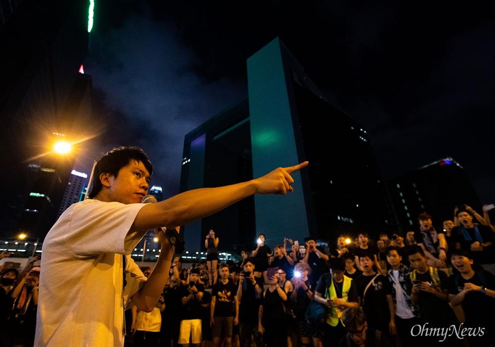범죄인 인도법 폐지를 촉구하는 반중국 집회 '검은 행진'이 끝난 16일 오후 민주당 소속 로이 궝천유 의워이 중앙정부로 모인 시위 참가자들을 향해 발언을 하고 있다. 로이 의원은 폭력 진압에 대한 경찰의 진정성 있는 사과, 캐리 람 행정장관의 사퇴 등을 촉구했다.