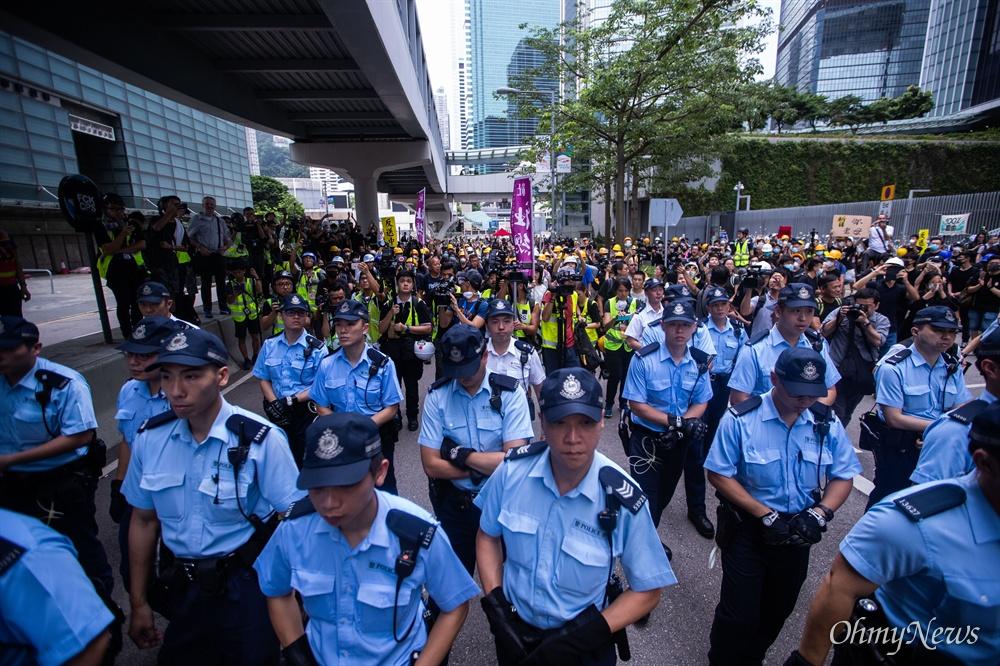 17일 오전 범죄인 인도법(일명 송환법) 폐지를 촉구하는 '검은 행진'에 참가한 홍콩 시민들에게 도로점거 철수를 요구하던 경찰들이 자리를 떠나고 있다.
