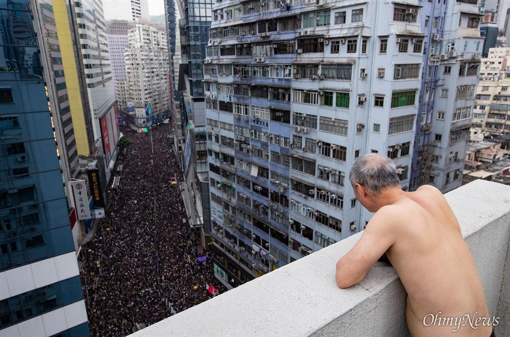 16일 오후 범죄인 인도법(일명 송환법) 폐지를 촉구하는 '검은 행진' 참가자들이 홍콩 중앙정부청사를 향해 행진하는 모습을 목씨가 아파트 옥상에서 구경하고 있다.
