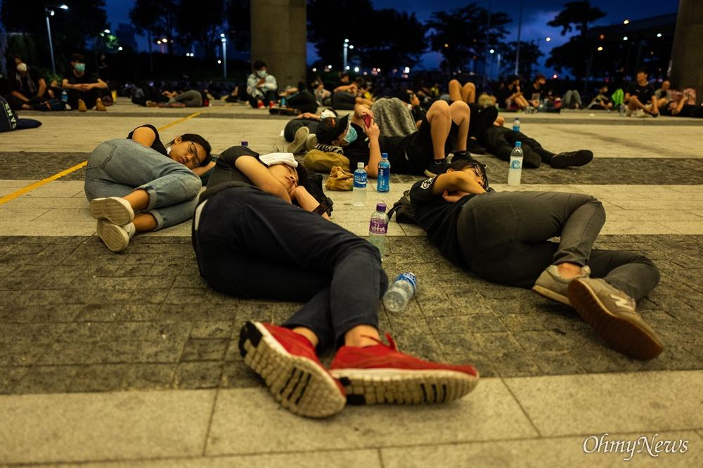 17일 오전 범죄인 인도법(일명 송환법) 폐지를 촉구하는 '검은 행진'에 참가한 홍콩 시민들이 중앙정부청사 내 광장에서 평화노래 밤샘 농성을 이어가던 시위 참가들이 바닥에 누워 쪽잠을 자고 있다.