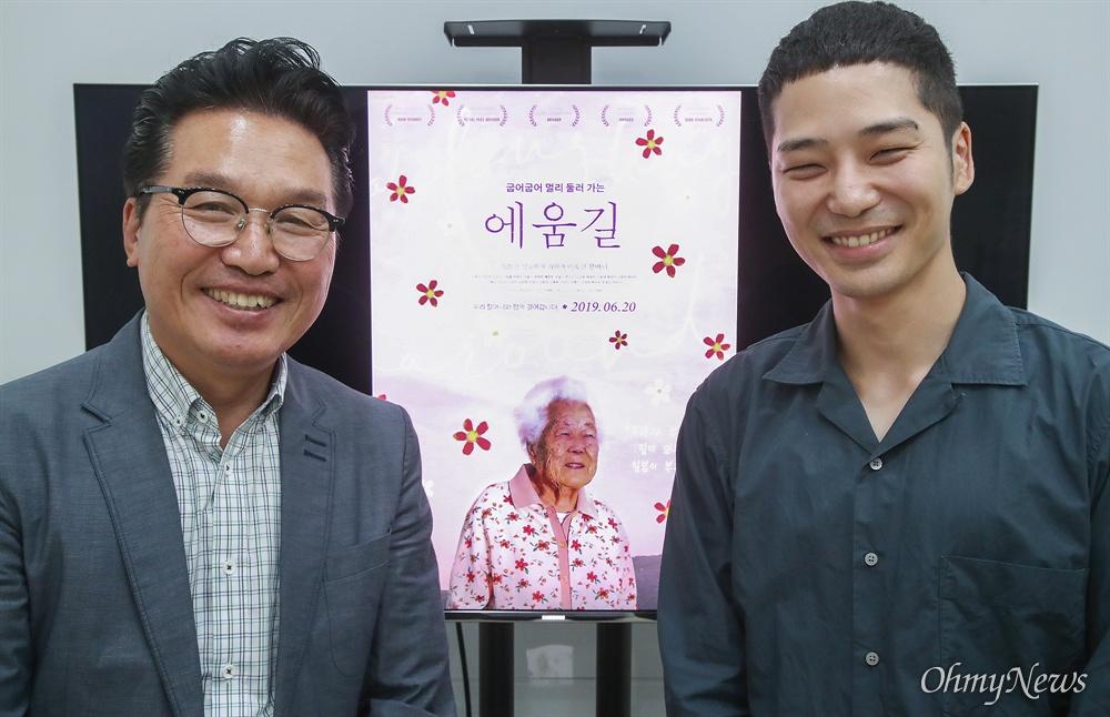 다큐멘터리 영화 <에움길>을 연출한 이승현 감독(오른쪽)과 안신권 나눔의 집 소장이 포스터 앞에서 환하게 웃으며 영화를 많이 봐달라고 부탁하고 있다. 영화 <에움길>은 일본군 성노예제 피해자 지원 시설인 '나눔의 집'에서 2000년대 초부터 20년간 할머니들을 촬영한 영상을 담은 다큐멘터리이다.