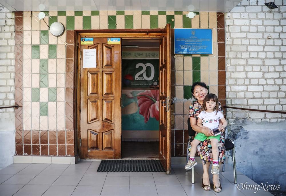 정수리 학교의 김 루드밀라 교장선생님이 손녀딸 김 리아(3세)와 함께 학교 정문 앞에서 기념사진을 찍고 있다.