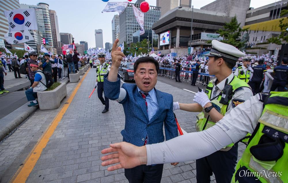 우리공화당 당원이 6일 오후 서울 광화문광장에서 2차 태극기 집회를 마치고 도로로 나와 항의를 하고 있다.