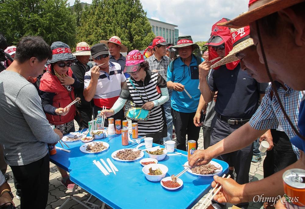 개 사육 농민 단체인 대한육견협회 회원들이 12일 오전 서울 여의도 국회 앞에서 개 식용 금지 법안 반대를 주장하며 개고기 시식 행사를 진행하고 있다.