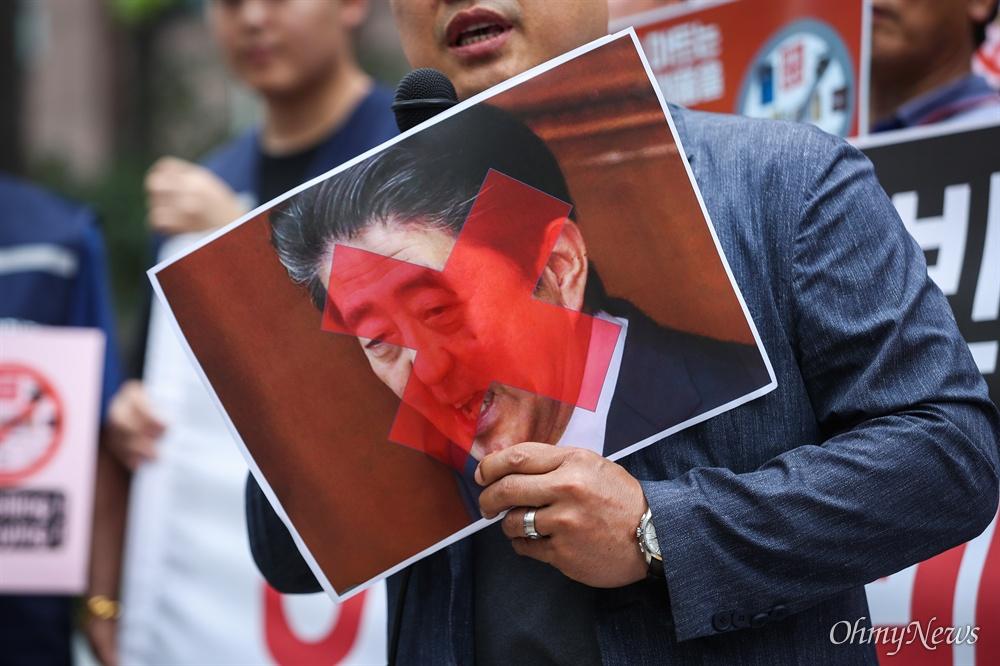 서울상인연합회, 한국마트협회 등 중소상인 자영업자 단체 회원들이 15일 오전 서울 종로구 일본대사관 인근에서 일본제품 판매 중단 확대 기자회견을 열고 붉은 엑스 표를 한 아베 일본 총리의 사진을 들고 있다.