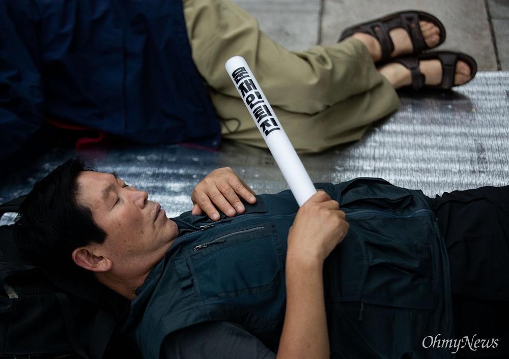 16일 오전 서울 광화문광장에서 천막농성 중이던 우리공화당 당원이 세종문화회관 계단에서 '문재인 퇴진'이 적힌 봉을 들고 잠들어 있다.