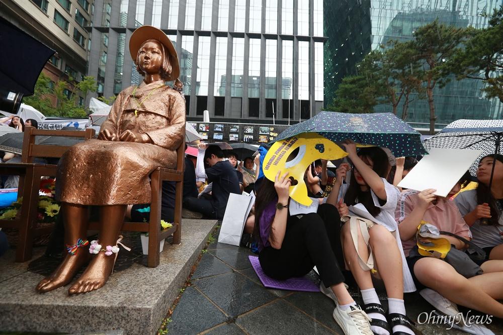세찬 소나기 속 수요시위 지키는 학생들 17일 오후 서울 종로구 일본대사관앞에서 1,396번째 일본군성노예문제 해결을 위한 수요시위가 열려, 일본의 진심어린 사죄와 최근 아베 정권의 경제보복을 규탄했다. 수요시위 직전 세차게 내리는 소나기에도 불구하고 학생들이 자리를 지키고 있다.