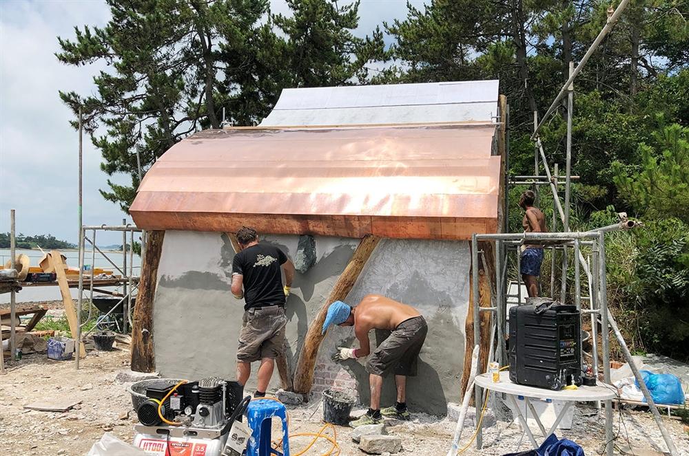 한낮의 땡볕 아래서 장 미쉘 팀이 청동 지붕을 한 작은 예배당 설치 작업을 하고 있다.