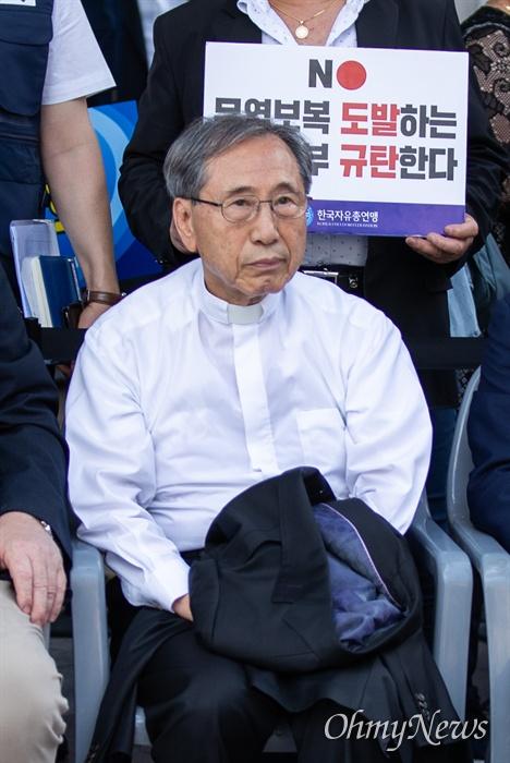 함세웅 신부가 13일 오후 서울 종로구 동화면세점 앞에서 열린 한국자유총연맹의 자유무역 파괴-경제침략 아베정권 규탄 집회에 참석하고 있다.