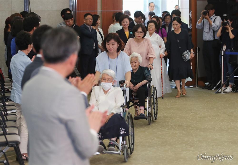 일본군 위안부 피해자 김경애, 이옥선, 이용수 할머니가 14일 오전 서울 용산구 백범김구기념관에서 열린 '일본군 위안부 피해자 기림의 날' 기념식에 입장하자, 참석자들이 기립해 반기고 있다.