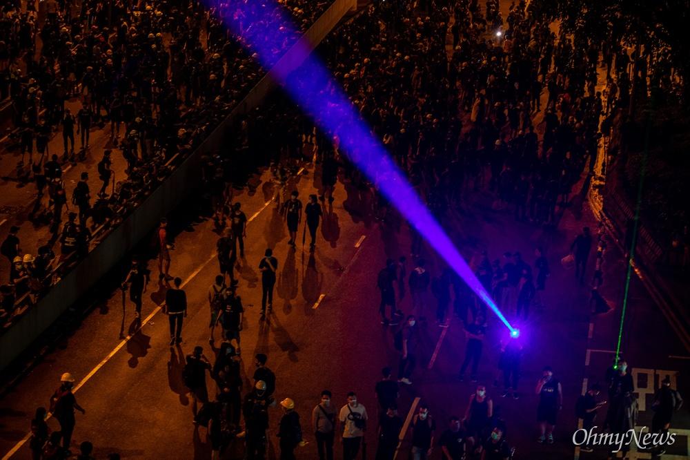 18일 오후 홍콩 중앙정부청사 앞에서 송환법 반대 및 강경진압 규탄 행진을 마친 시위 참가자들이 정부청사를 향해 레이저 포인터를 쏘고 있다.