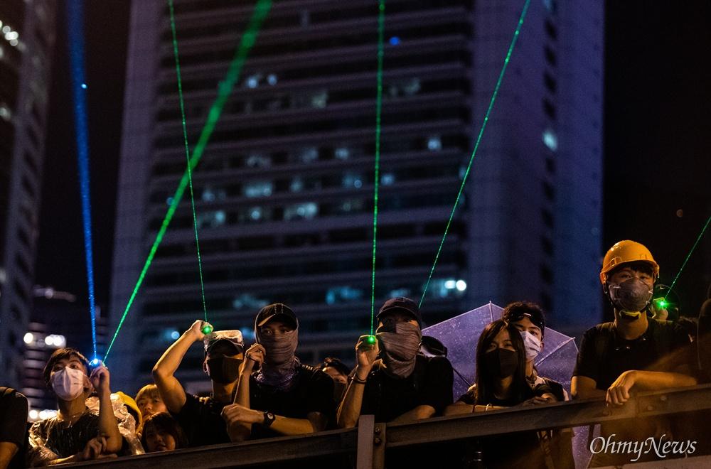 레이저 포인터 쏘는 홍콩시민들 18일 오후 홍콩 중앙정부청사 앞에서 송환법 반대 및 강경진압 규탄 행진을 마친 시위 참가자들이 정부청사를 향해 레이저 포인터를 쏘고 있다.