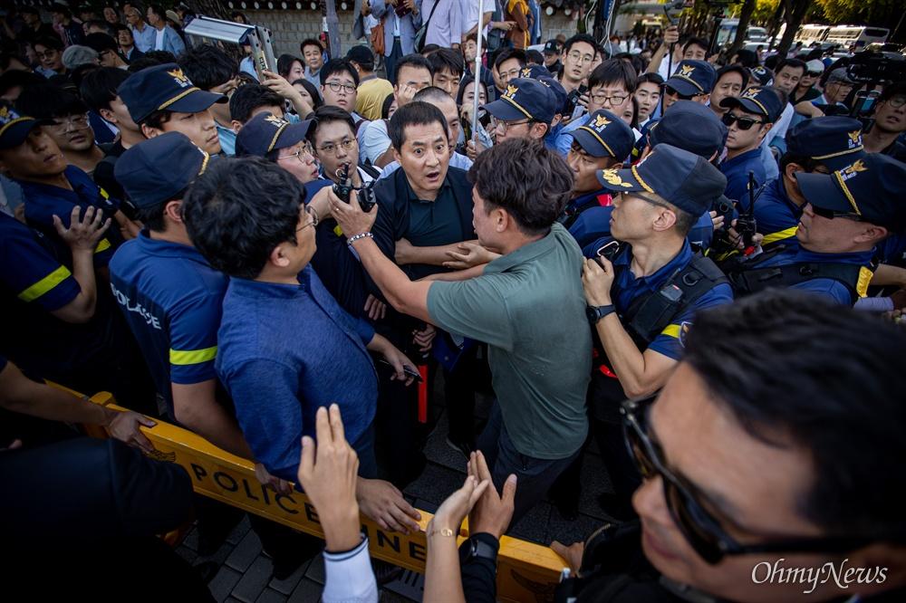 자유한국당 박대출 의원이 16일 오후 서울 청와대 분수대 인근에서 황교안 자유한국당 대표 삭발식 장소에 들어가려는 기자, 개인방송 유튜버, 지지자 등과 뒤섞여 출입을 통제하는 경찰에게 항의하고 있다.