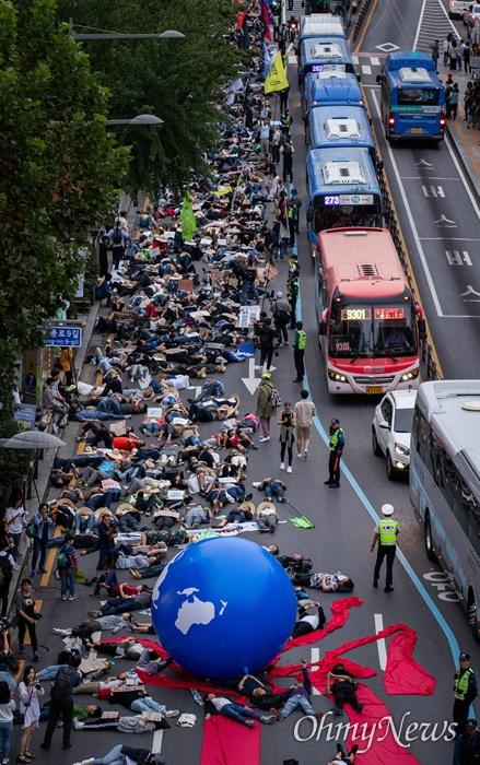 국제 기후 파업 주간인 21일 오후 서울 종각역 사거리에서 열린 9.21 기후위기 비상행동에서 참가자들이 '기후 위기가 다가오면 생존의 위협이 다가온다'는 의미를 가진 퍼포먼스를 하고 있다.