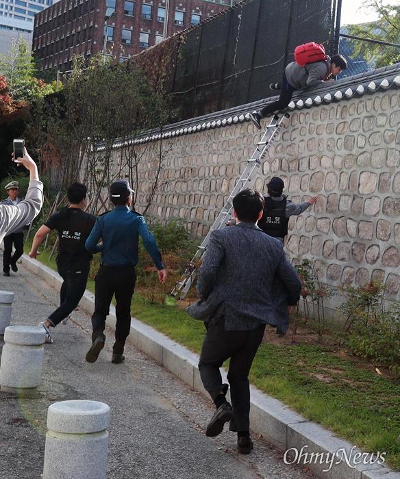 '월담시위' 대학생, 뒤쫓는 경찰 한국대학생진보연합 소속 대학생들이 과도한 주한미군 방위금 분담금(6조) 요구에 항의하며 18일 오후 서울 중구 덕수궁 뒤편 미대사관저 담장에 사다리를 놓고 넘어들어가는 기습 시위를 벌였다.