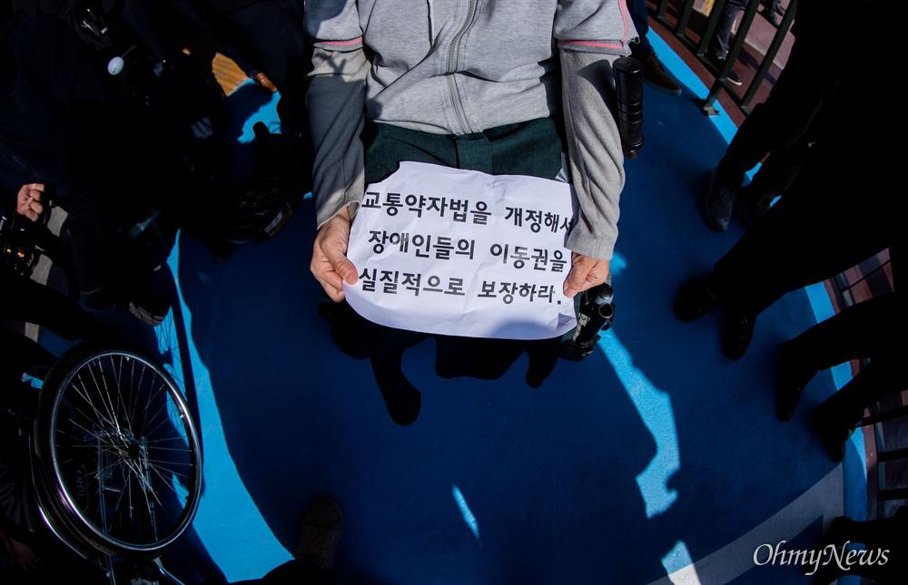 휠체어탑승가능 고속버스가 운행을 시작하는 28일 오전 서울 서초구 고속버스터미널 경부선 휠체어 승강장에서 첫 승객이 강릉행 버스에 탑승하는 동안 문애린 서울장애인차별철폐연대 상임대표가 손피켓을 들고 있다.