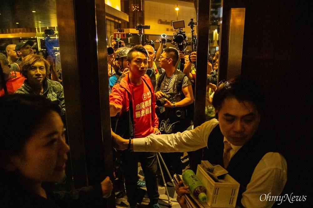 지미 샴(Jimmy Sham, 岑子杰)이 당선된 직후 홍콩 이공대에서 벌어진 고립 학생 구조 집회에 참가하던 중 시위대 사이에서 경찰 결혼식에 참석했던 한 시민을 이동시키고 있다.