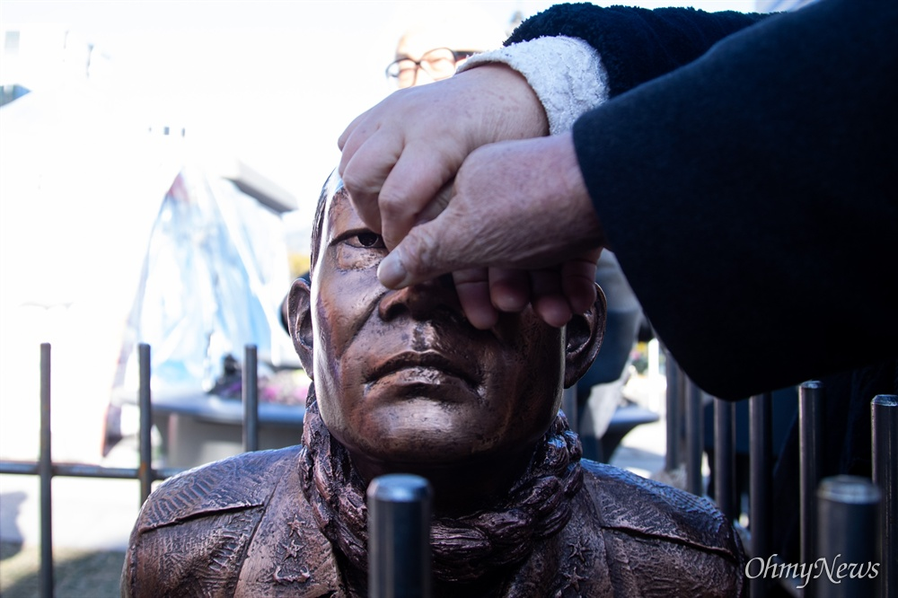 518 관련 시민단체 회원들이 12일 오전 서울 광화문광장에서 전두환 구속과 처벌을 기원하는 '구속된 전두환' 동상을 설치하고 전 씨 코를 비틀고 있다.