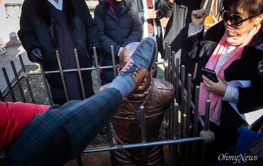 518 관련 시민단체 회원들이 12일 오전 서울 광화문광장에서 전두환 구속과 처벌을 기원하는 '구속된 전두환' 동상을 설치하고 손과 발로 매질 하고 있다.
