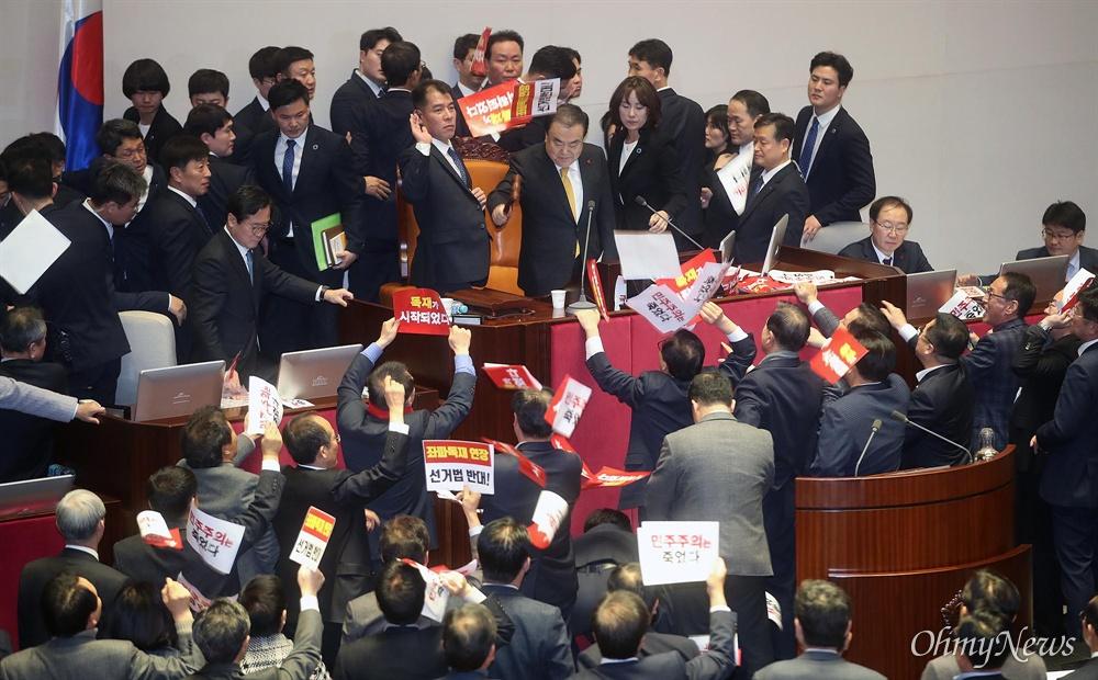 문희상 국회의장이 27일 오후 서울 여의도 국회 본회의장에서 공직선거법 개정안을 찬성 156, 반대 10, 기권 1표로 통과시키자, 자유한국당 의원들이 피켓을 던지며 항의하고 있다.